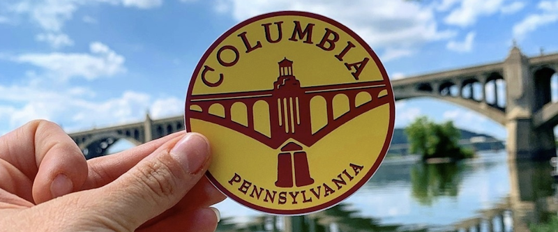 a hand holds a sticker, the prize for completing at least five challenges on the Columbia bucket list. There's a bridge over a river in the background.