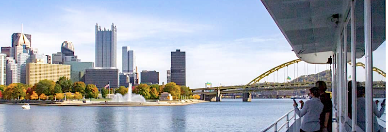 the Pittsburgh skyline and one of its iconic bridges are viewed from a river boat