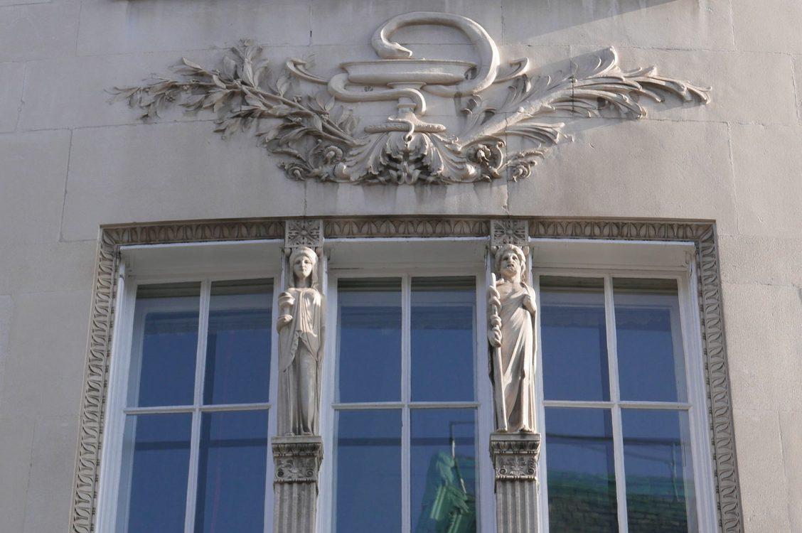 Greek gods on stone building facade.
