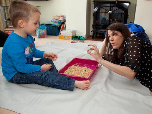 Billede af et barn, der leger på gulvet sammen med voksen, der opmærksom og fokuseret på barnet.