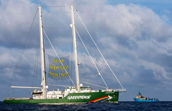 """Greenpeace International activists aboard the Rainbow Warrior display banners reading """"Stop Deep Sea Mining"""" in front of the Maersk Launcher, a ship chartered by DeepGreen, one of the companies spearheading the drive to mine the barely understood deep sea ecosystem.PHOTOGRAPH: MARTEN VAN DIJL/GREENPEACE"""