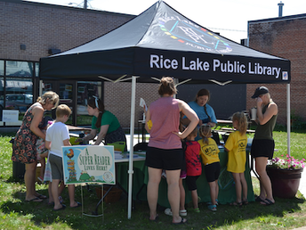 Adults and children standing around an outdoor tent talking to librarians