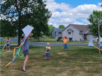 Adults and children flying kites in an open space